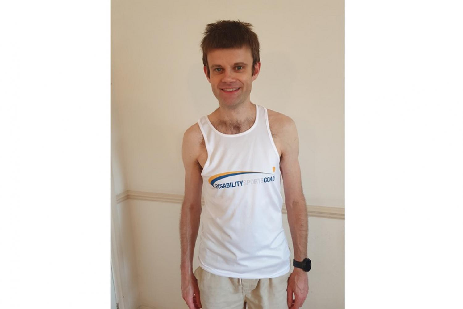 Sam Vardy smiling at the camera while wearing a running vest with the logo of Disability Sports Coach